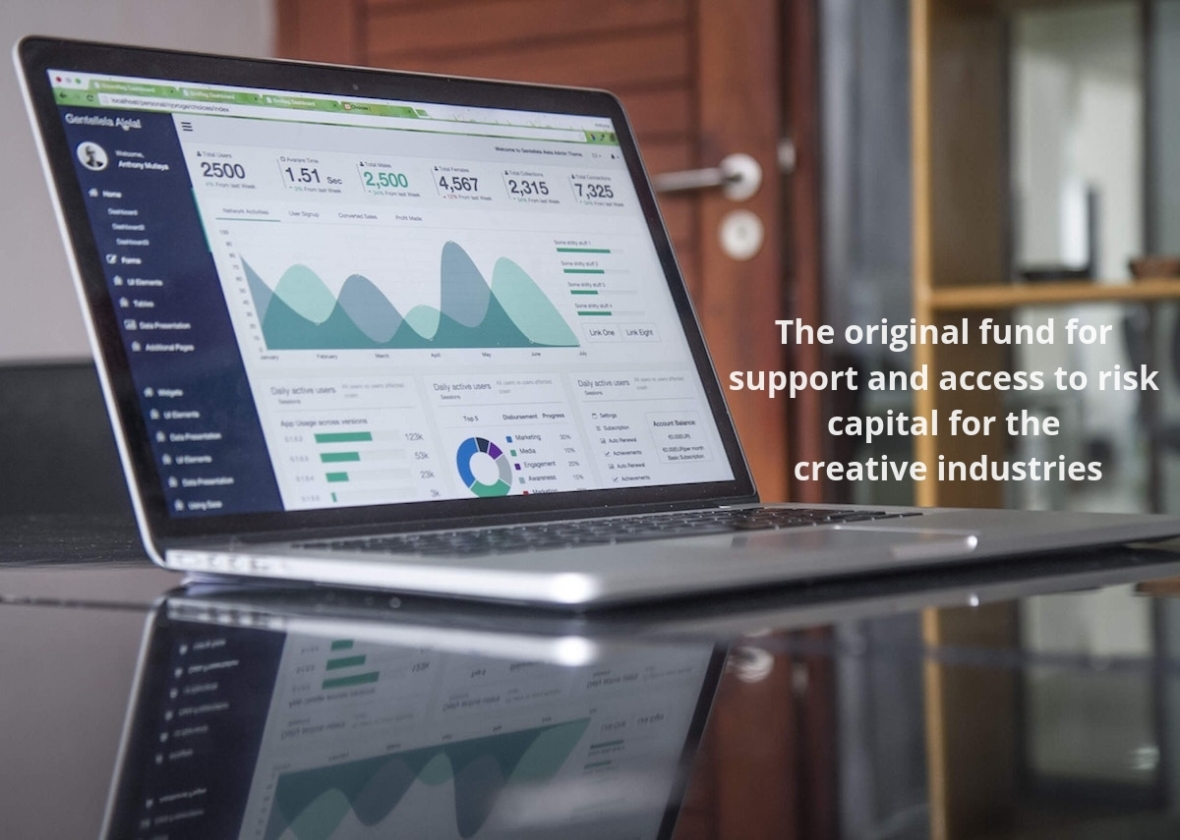"""an open laptop displaying financial statistics on a desk, with an office door and shelving in the background. The CAF tagline is overlaid """"The original fund for support and access to risk capital for the creative industries"""""""